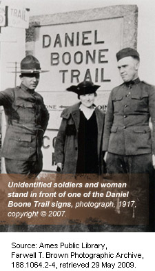 Two unidentified soldiers and woman in front of Daniel Boone Trail sign